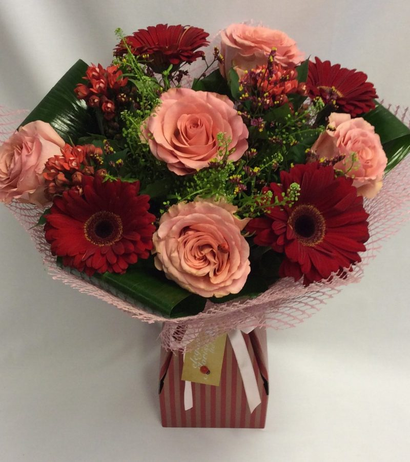This stunning handtied is a mix of classic red and peach colours, including roses, gerberas and thaspelli greens. This is perfect for all occasions, including romantic, anniversary or birthdays.